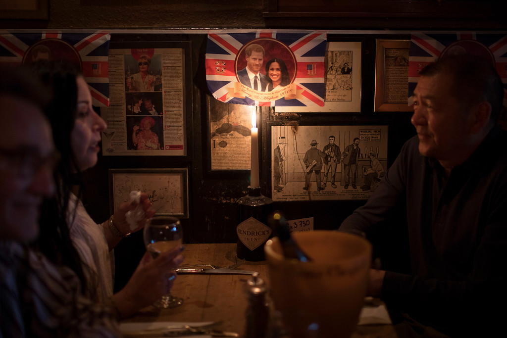. People sit inside a pub decorated with bunting featuring the image of Prince Harry and Meghan Markle in Windsor, England, Wednesday, May 16, 2018. Preparations continue in Windsor ahead of the royal wedding of Britain\'s Prince Harry and Meghan Markle on Saturday May 19. (AP Photo/Emilio Morenatti)