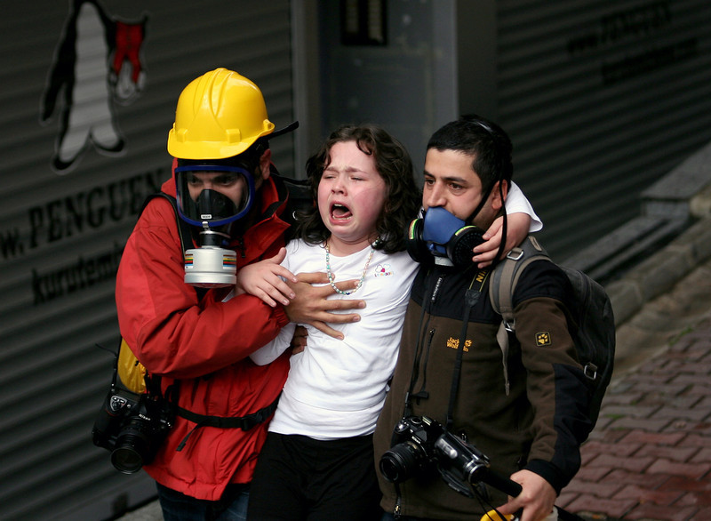 . People help a child affected by teargas as riot police use water cannons and teargas to disperse thousands of people trying to reach the city\'s main Taksim Square to celebrate May Day in Istanbul, Turkey, Thursday, May 1, 2014. Clashes erupted between May Day demonstrators and riot police as crowds determined to defy a government ban tried to march to the city\'s iconic Taksim Square. Security forces pushed back demonstrators with water cannons and tear gas. (AP Photo/Emrah Gurel)