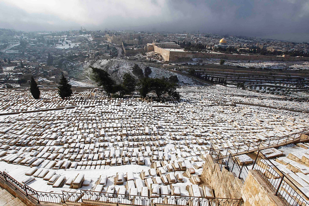 . Snow covers the Jewish cemetery on the Mount of Olives  and the Dome of the Rock on the compound known to Muslims as al-Haram al-Sharif and to Jews as Temple Mount, in Jerusalem on January 10, 2013. The worst snowstorm in 20 years shut government offices, public transport and schools in Jerusalem and along the northern Israeli region bordering on Lebanon on Thursday.  REUTERS/Baz Ratner