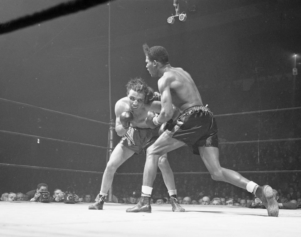 . FILE - In this Feb. 23, 1945, file photo, Jake LaMotta, left, of the Bronx borough of New York, and Ray Robinson of the Harlem section of New York, fight at Madison Square Garden in New York. Robinson won the fight on a decision. LaMotta fought Sugar Ray Robinson six times, handing Robinson his first defeat. LaMotta, whose life was depicted in the film �Raging Bull,� died Tuesday, Sept. 19, 2017, at a Miami-area hospital from complications of pneumonia. He was 95. (AP Photo/Matty Zimmerman, File)