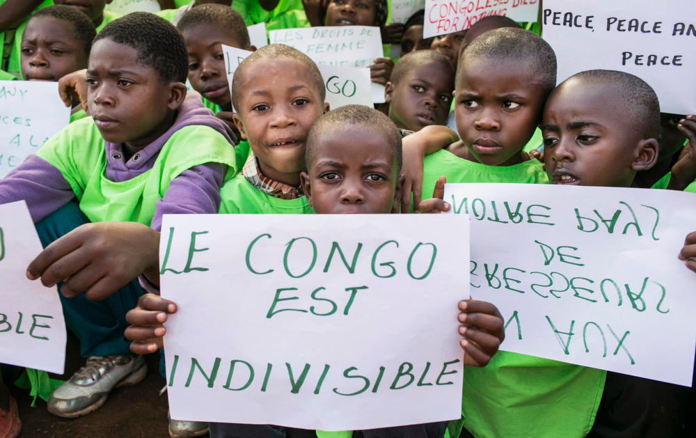 Description of . Congolese children hold a placard that reads