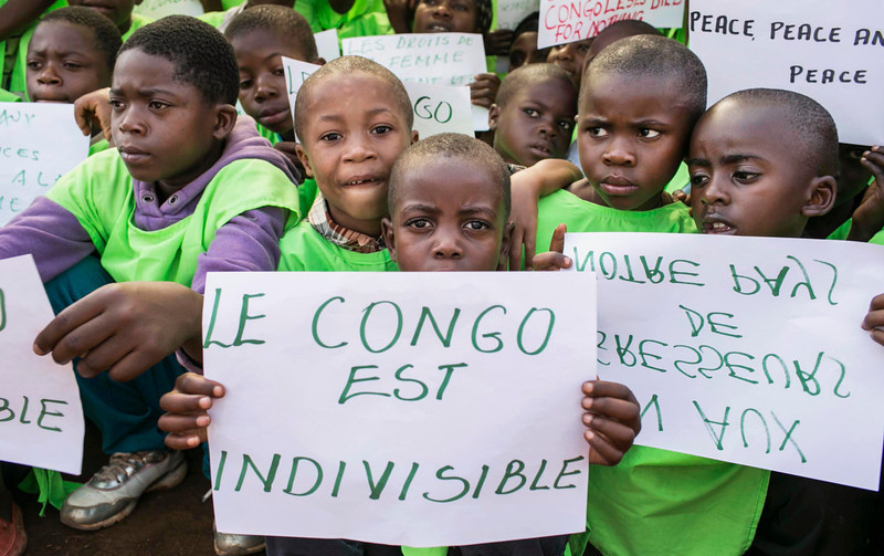 ". Congolese children hold a placard that reads ""the Congo is indivisible\"" during a global rally \""One Billion Rising\"", which is part of a V-Day event calling for an end to gender-based violence, in Bukavu February 14, 2013. V-Day is a global activist movement to end violence against women and girls. REUTERS/Jana Asenbrennerova"