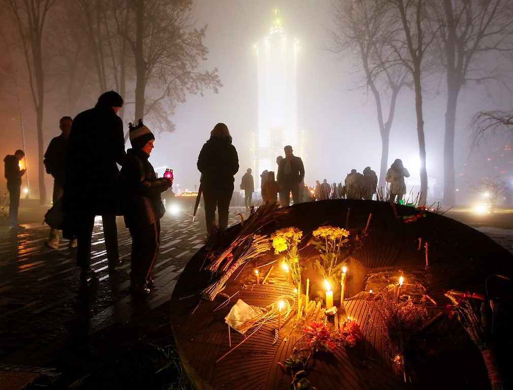 . Ukrainians light candles during a memorial ceremony near of a monument to the victims of the Great Famine in Kiev, 23 November 2013. Reports state that Ukrainians light candles to mark a day of memory for the victims of the Holodomor in 1932-1933.   EPA/SERGEY DOLZHENKO