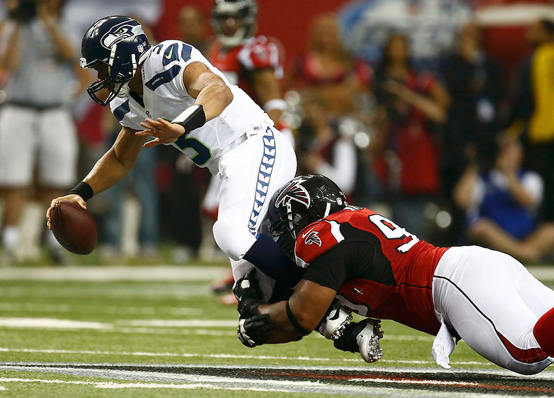 . Seattle Seahawks quarterback Russell Wilson (L) is sacked by Atlanta Falcons defensive end Vance Walker during the third quarter in their NFL NFC Divisional playoff football game in Atlanta, Georgia January 13, 2013.  REUTERS/Chris Keane
