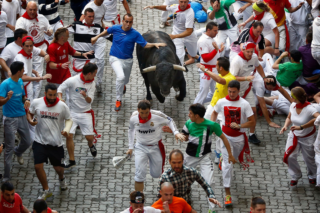 ". Revelers are chased by a Victoriano del Rio ranch fighting bull during the running of the bulls at the San Fermin festival, in Pamplona, Spain, Wednesday, July 10, 2013. Revelers from around the world arrive to Pamplona every year to take part in some of the eight days of the running of the bulls glorified by Ernest Hemingway\'s 1926 novel ""The Sun Also Rises.\"" (AP Photo/Daniel Ochoa de Olza)"