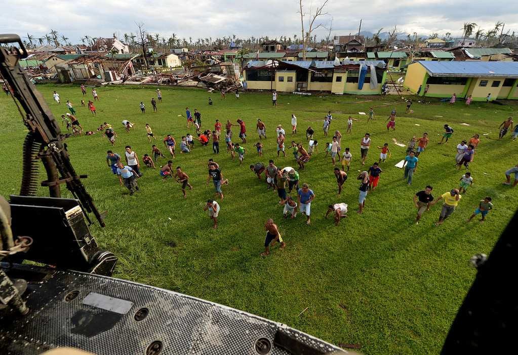 . Villagers rush to retrieve relief aid delivered by a Huey helicopter from the Philippines Air Force in a village near Tacloban on November 17, 2013. Grieving survivors of a monster typhoon in the mainly Catholic Philippines flocked to shattered churches on November 17, listening to soothing sermons and asking questions of God nine days after the storm ripped their communities apart.    MARK RALSTON/AFP/Getty Images