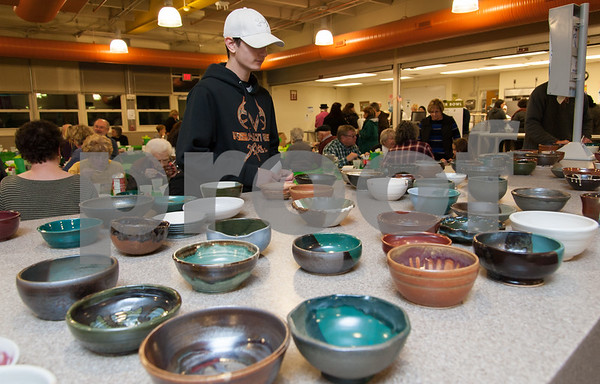 01/31/18 Wesley Bunnell | Staff The Friendship Service Center held their first ever Souper Bowl at E.C. Goodwin on Wednesday evening to raise awareness of hunger and provide funding their soup kitchen. Guests were able to buy a handcrafted ceramic bowl made by Central Connecticut State University art students as the entrance fee and have it filled with the soup of their choice. Students from E.C. Goodwins culinary department handled the serving of the soups. Adam Young, V.P. of the National Honor Society, looks over the bowls available after spending the evening volunteering and looking over the tables.