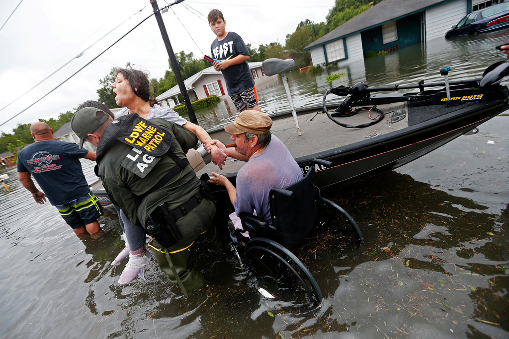 . Members of the Louisiana Department of Wildlife and Fisheries help rescue Mike Henry, right, and his partner Rosemarie Carpenter during flooding from Tropical Storm Harvey in Orange, Texas, Wednesday, Aug. 30, 2017. (AP Photo/Gerald Herbert)
