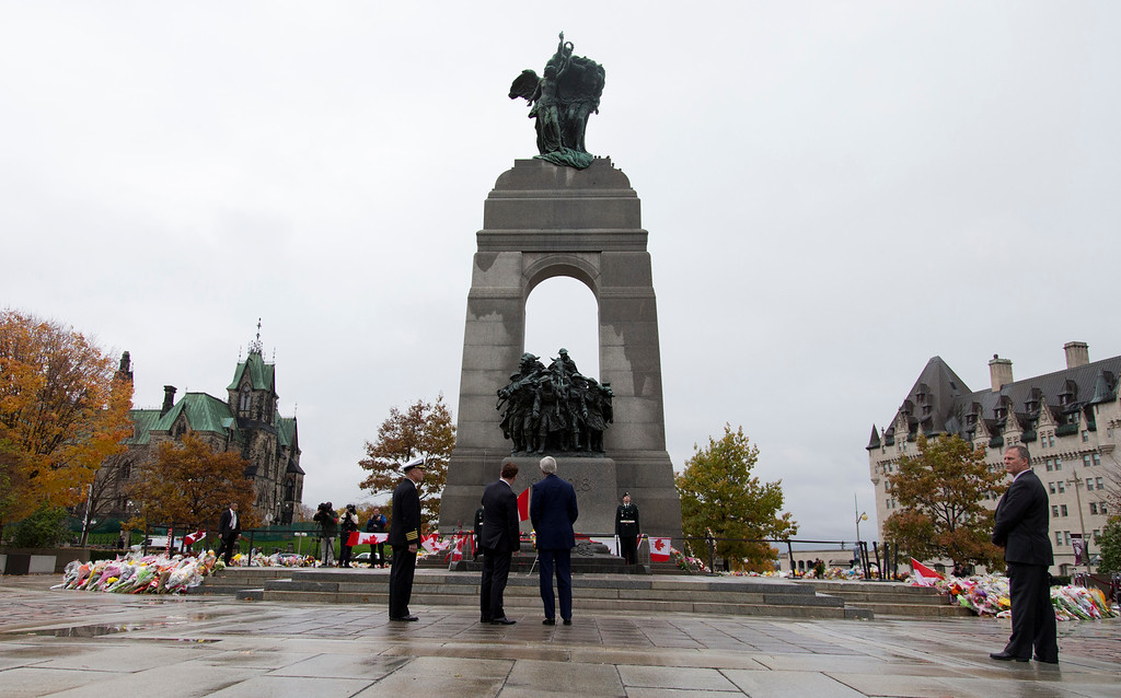 . From left, U.S. Naval Attache, Capt. Charles J. Cassidy, Canadian Foreign Minister John Baird, and Secretary of State John Kerry, pause after placing a wreath at the Tomb of the Unknown Soldier during a ceremony at the National War Memorial in Ottawa, Canada, Tuesday, Oct. 28, 2014. (AP Photo/Carolyn Kaster, Pool)