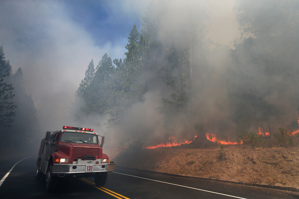 . A fire truck drives past burning trees as firefighters continue to battle the Rim Fire near Yosemite National Park, Calif., on Monday, Aug. 26, 2013. Crews working to contain one of California\'s largest-ever wildfires gained some ground Monday against the flames threatening San Francisco\'s water supply, several towns near Yosemite National Park and historic giant sequoias. (AP Photo/Jae C. Hong)