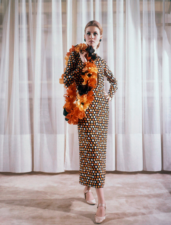 . Paris Couturier Yves Saint Laurent displayed this cocktail dress with his now length at mid-calf at the Paris Spring and Summer showings in 1969. It is of orange and black printed crape de china worn with a boa of orange flowers matching the dress sandals are of beige satin. (AP Photo)
