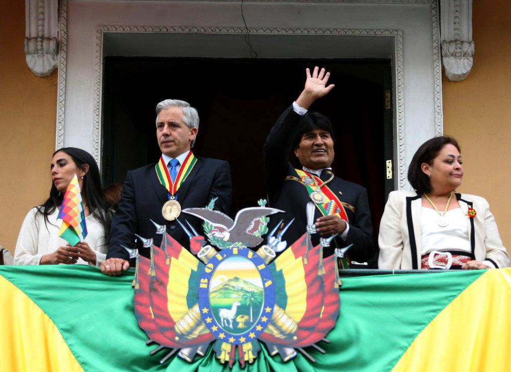 Description of . Bolivia's President Evo Morales (2nd R) waves while Senator Gabriela Montano (L) Vice President Alvaro Garcia Linera (2nd L) and Betty Tejada, president of the Chamber of Deputies, look on during celebrations commemorating Morales' eighth continuous year of government, in La Paz January 22, 2013. Morales, Bolivia's first indigenous president, took office on January 22, 2006, after winning the presidential election with 53.7% and he was re-elected for a second term on 2010-2015 with 64% of the votes according local media. REUTERS/Gaston Brito