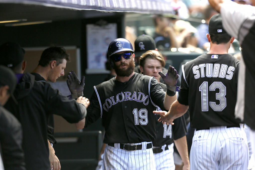 . Colorado Rockies center fielder Charlie Blackmon #19 high fives his teammates after scoring a run in the bottom of the 4th inning against the Chicago Cubs at Coors Field on August 7, 2014 in Denver, Colorado.  The Chicago Cubs defeated the Colorado Rockies 6-2. (Photo by Trevor Brown, Jr./Getty Images)