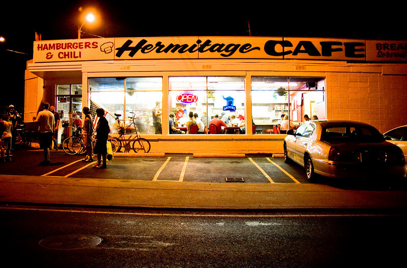 """A group of bicyclists hangs out past midnight at Hermitage Cafe in downtown Nashville after the July 4th fireworks.  The group could be seen riding downtown before the fireworks - the double-tall bicycle with a large American flag drawing a lot of attention.  This cafe is featured at the beginning of Sugerland's  """"Baby Girl"""" music video."""