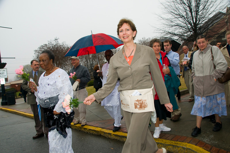 Linda Fuller wears Memorial Celebration commentrative nail apron as she helps lead march. sh
