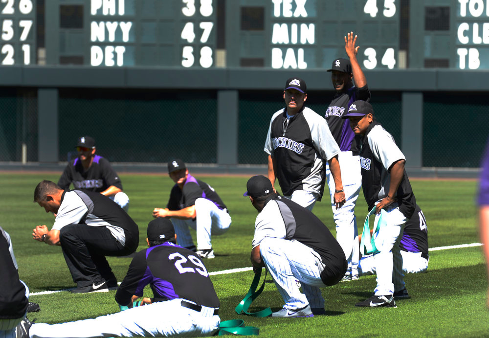 . Edgmer Escalona (44) raises his hand as he gestures towards Juan Nicasio squatting down with exercise band after an argument broke out between the two pitchers during stretching exercises. Manager Walt Weiss talked with both pitchers after practice. The Colorado Rockies held an open practice for the fans April 4, 2013 at Coors Field. (Photo By John Leyba/The Denver Post)