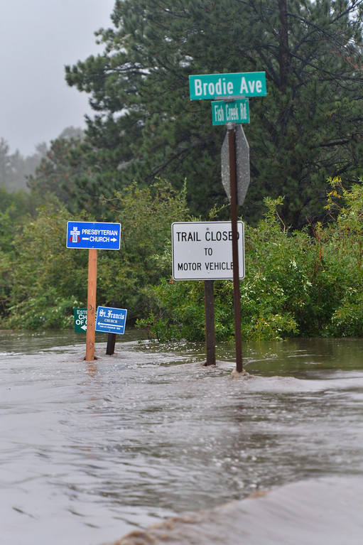 . Signs stick out of the flood waters of Fish Creek Road on Thursday, September 12, 2013. The intersection was closed and eventually collapsed in the flood waters. Walt Hester/Estes Park Trail-Gazette