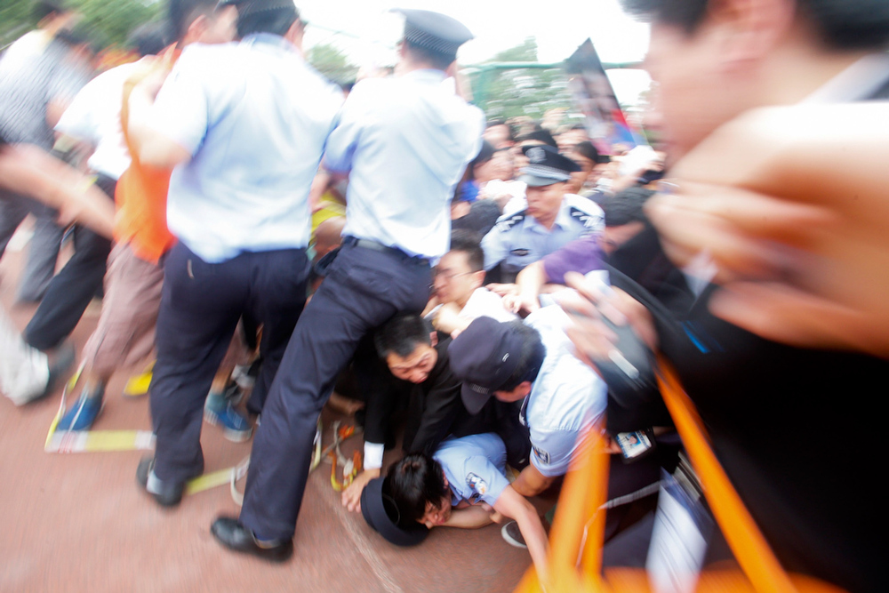 . Police officers fail to stop people from falling to the ground in a crush as they surge forward as David Beckham arrives at Tongji University on June 20, 2013 in Shanghai, China. The stampede is reported to have left five people injured and hospitalised. (Photo by Getty Images)
