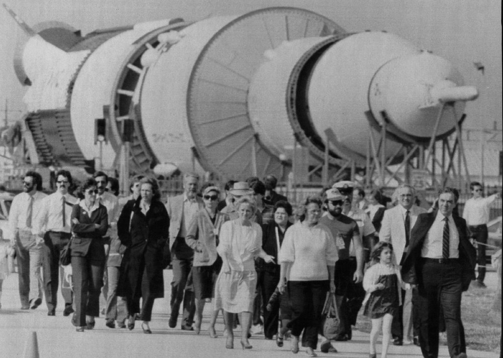 Description of . Workers and their families at the Kennedy Space Center stream past a Saturn 5 rocket on their way to a memorial service on Feb. 1, 1986 for the 7 astronauts that were killed aboard the shuttle Challenger.  Denver Post Library Archive