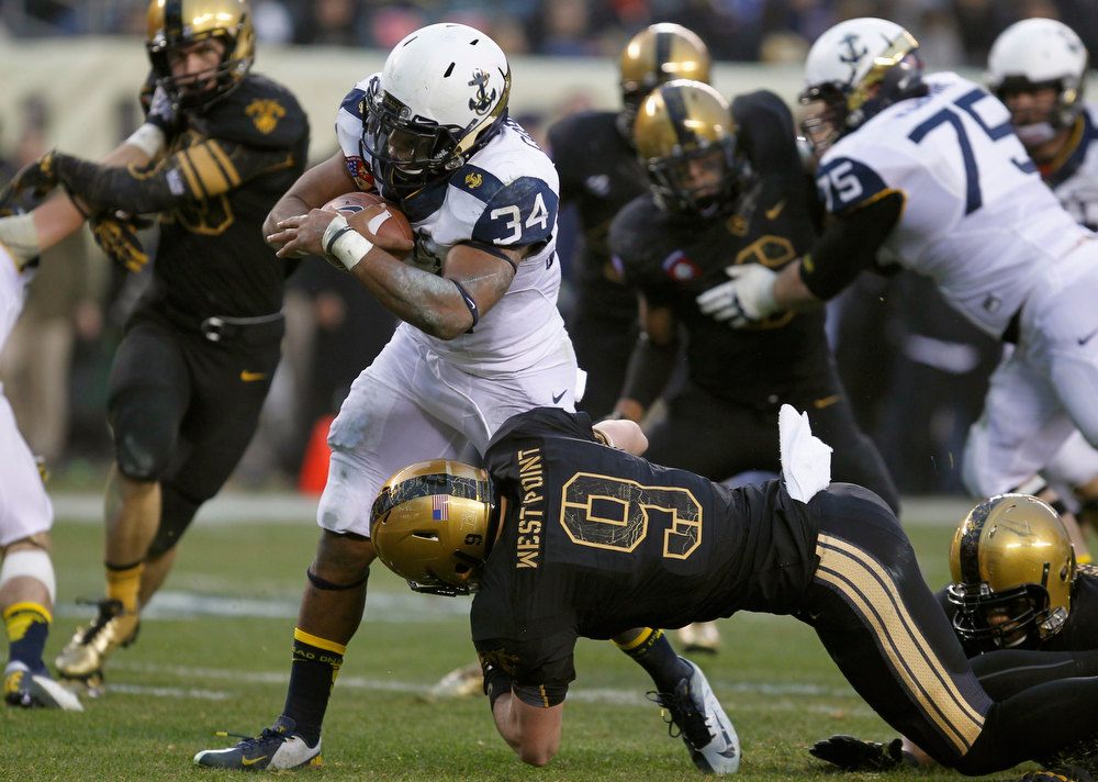 . Navy fullback Noah Copeland (34) scores a touchdown as Army defender Hayden Pierce (9) tries to make the tackle during the second quarter of the Army versus Navy NCAA football game in Philadelphia, Pennsylvania, December 8, 2012. REUTERS/Tim Shaffer