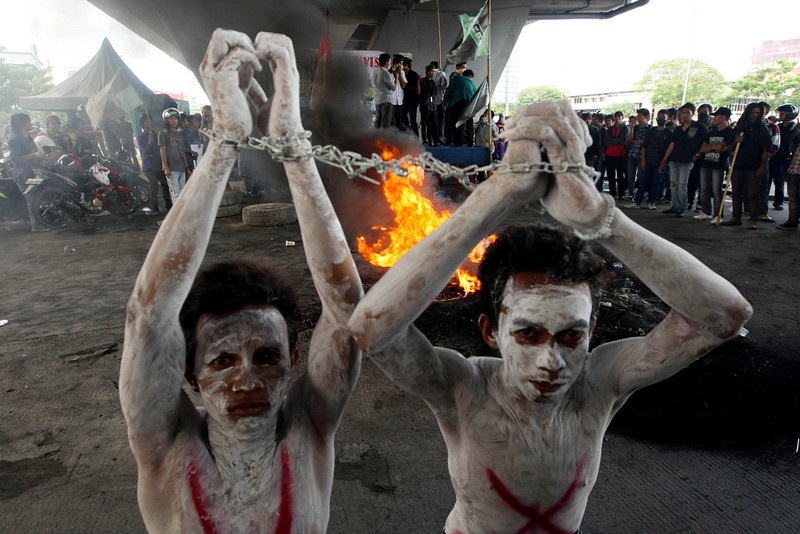 . Indonesian students perform as suspects in corruption arrested during an anti-government protest to mark International Anti Corruption Day in Makassar, South Sulawesi, Indonesia, Monday, Dec 10, 2012. Protesters staged the protest accusing the government of failing to fight corruption and improve human rights. (AP Photo/Abbas Sadji)