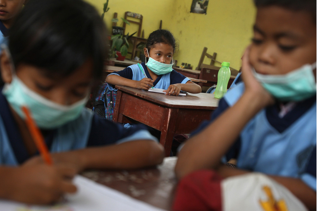 . Students wear masks to protect their respiration from the volcanic ash from the eruption of Mount Sinabung at an elementary school in Tiga Nderket, North Sumatra, Indonesia, Wednesday, Nov. 6, 2013. (AP Photo/Binsar Bakkara)
