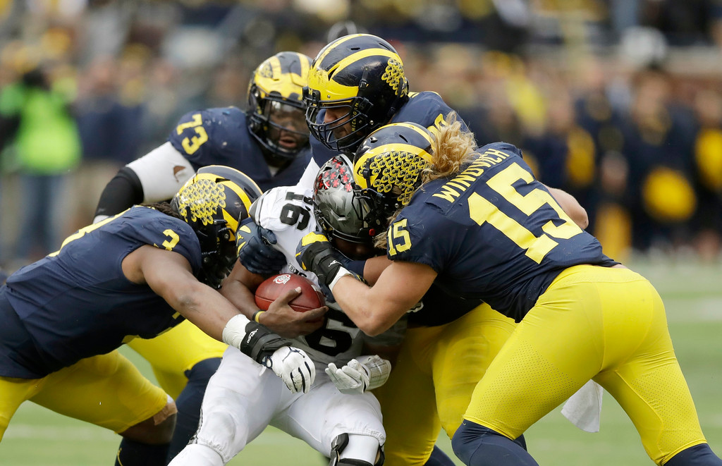 . Ohio State quarterback J.T. Barrett (16) is sacked by Michigan defensive lineman Rashan Gary (3) and defensive lineman Chase Winovich (15) during the second half of an NCAA college football game, Saturday, Nov. 25, 2017, in Ann Arbor, Mich. Barrett did not return after the sack. (AP Photo/Carlos Osorio)