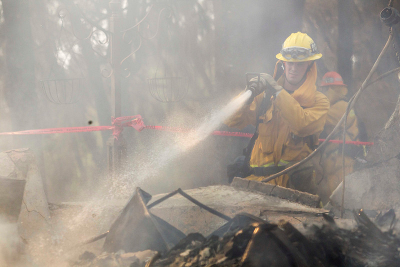 . A firefighter puts out hot spots at the Singer Mansion after it burned down during a wildfire just north of the San Gabriel Valley community of Glendora, Calif., on Thursday, Jan 16, 2014. Southern California authorities have ordered the evacuation of homes at the edge of a fast-moving wildfire burning in the dangerously dry foothills of the San Gabriel Mountains. (AP Photo/Ringo H.W. Chiu)