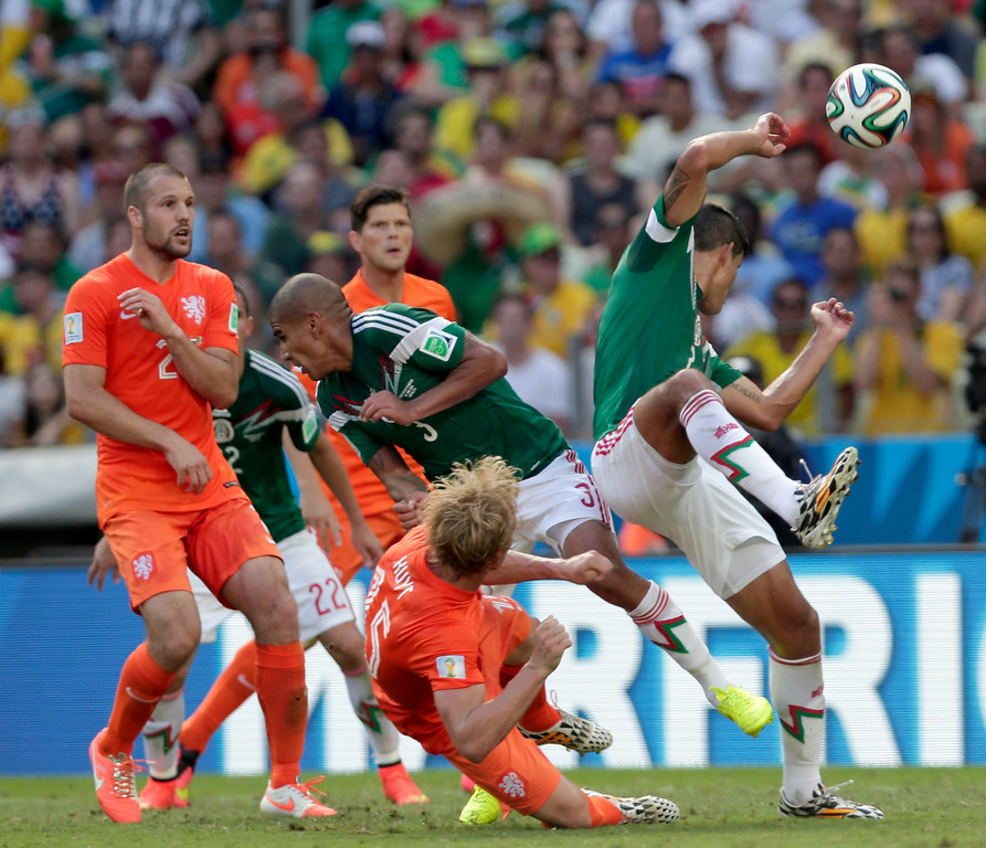 . Netherlands\' Dirk Kuyt, down, fights for the ball with Mexico\'s defenders during the World Cup round of 16 soccer match between the Netherlands and Mexico at the Arena Castelao in Fortaleza, Brazil, Sunday, June 29, 2014. (AP Photo/Marcio Jose Sanchez)