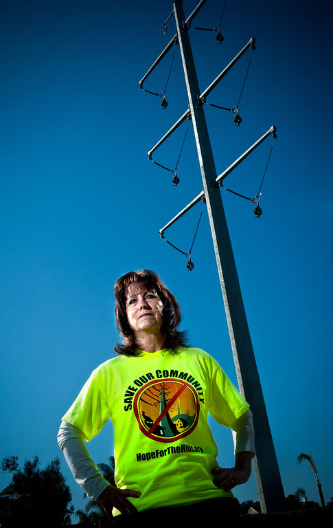 . Joanne Genis, of Chino Hills, stands in the shadow of one of the Tehachapi high-voltage power transmission lines towers as she stands in her front yard of her home in Chino Hills.  (Staff photo/Inland Valley Daily Bulletin)