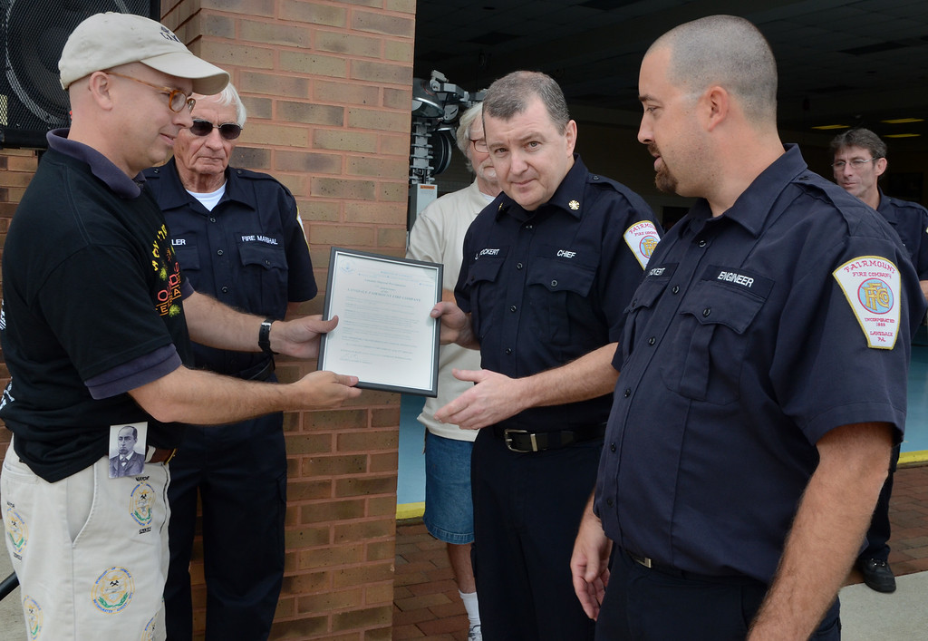 . Lansdale Mayor Andy Szekely ,L, presents a proclamation to Fairmount Fire Company Chief Joe Stockert (center) President Ian Fickert (R) and Fire Marshall Jay Davelar (2nd from L) in recognition of the companies 125th Anniversary during the Lansdale Founders Day celebration on Saturday August 23,2014. Photo by Mark C Psoras/The Reporter