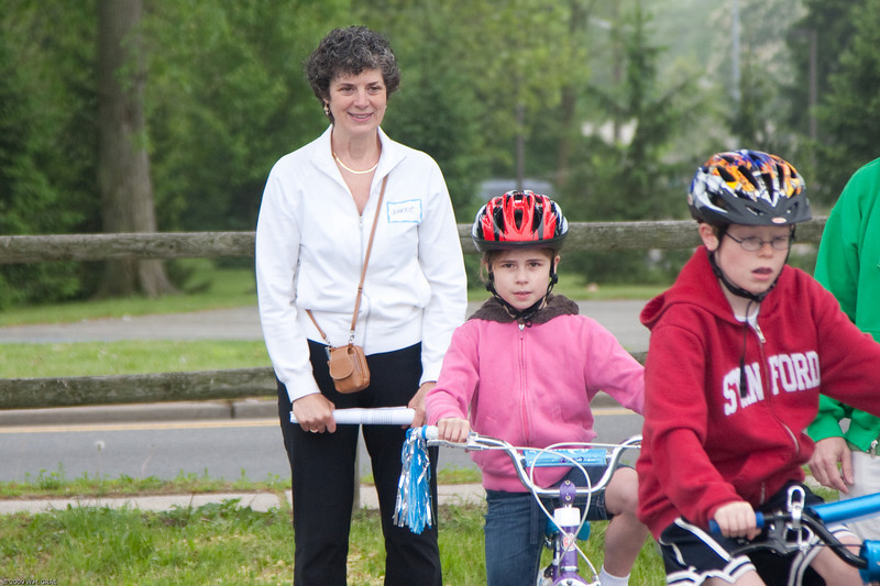 (1) Pslip Slug #: W 00019652; (2) Ridgewood, NJ; (3) 05/16/09; (4) Bike Rodeo and Safety Fair; (5) Volunteer Joanne Stolfo looks on as Elizabeth Flynn and Will Gagan demonstrate bicycling skills while moving through an obstacle course; (6) W.H. Grae for the Ridgewood News.