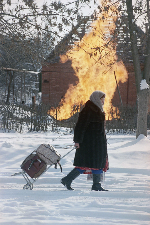 . An elderly woman leaves Grozny with her belongings during a lull in fighting on Saturday, Jan. 21, 1995, back dropped by the flames of a burning gas pipe which was set ablaze by shelling. Russian forces resumed their shelling of Grozny, but also trained guns on an outlying village in a sign that both sides may be expanding the war to the countryside. (AP Photo/Peter Dejong)