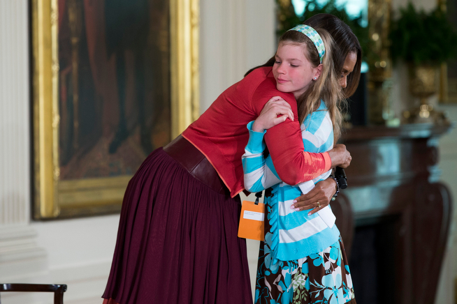 """. First lady Michelle Obama hugs Charlotte Bell, 10, after she handed Mrs. Obama her dad\'s resume during the White House\'s annual \""""Take Our Daughters and Sons to Work Day,\"""" Thursday, April 24, 2014, in the East Room of the White House in Washington. The girl in the front row at Thursday�s event told the first lady that her dad had been out of work for three years. Then the girl popped up to hand Mrs. Obama her dad�s resume saying �My dad�s been out of a job for three years and I wanted to give you his resume.� (AP Photo/ Evan Vucci)"""