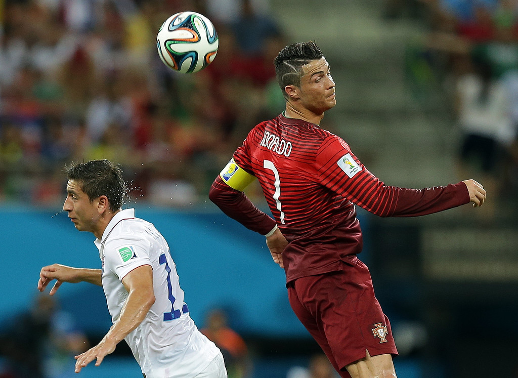 . Portugal\'s Cristiano Ronaldo heads the ball over United States\' Alejandro Bedoya during the group G World Cup soccer match between the USA and Portugal at the Arena da Amazonia in Manaus, Brazil, Sunday, June 22, 2014. (AP Photo/Martin Mejia)