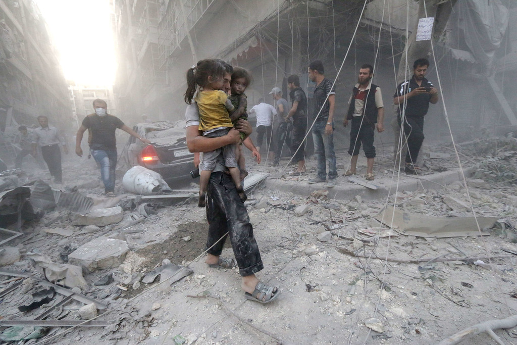 ". A Syrian man carries two girls covered with dust following a reported air strike by government forces on July 9, 2014 in the northern city of Aleppo. According to the Syrian Observatory for Human Rights, by May some 2,000 civilians including 500 children had been killed in the daily air strikes, which rights groups have condemned as a ""war crime\"" for failing to discriminate between military and civilian targets. AFP PHOTO /AMC/ZEIN  AL-RIFAI/AFP/Getty Images"