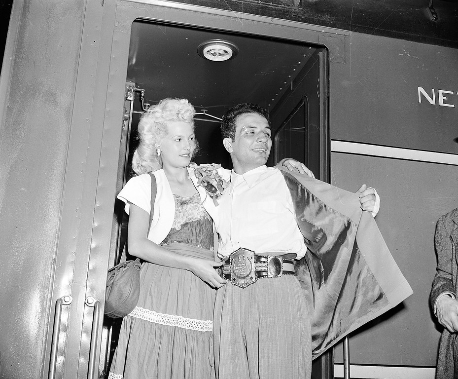 . FILE - In this June 18, 1949, file photo, newly crowned World Middleweight Boxing Champion Jake LaMotta, accompanied by his wife Vicky, arrives at Grand Central Terminal in New York after defeating Marcel Cerdan in Detroit on June 16. LaMotta, whose life was depicted in the film �Raging Bull,� died Tuesday, Sept. 19, 2017, at a Miami-area hospital from complications of pneumonia. He was 95. (AP Photo/File)
