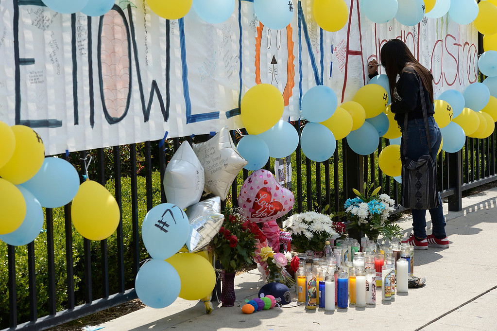 . Sarah Baiza,15, writes on the memorial. Students at El Monte High School brought flowers, candles and other items in remembering Adrian Castro, a Senior student who was killed in bus crash in Northern California that took the lives of 10 people. El Monte, CA. 4/13/2014(Photo by John McCoy / Los Angeles Daily News)