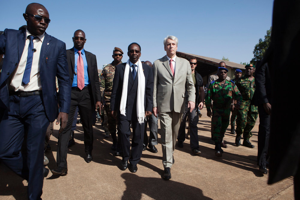Description of . Malian President Dioncounda Traore (white scarf) and French ambassador to Mali Christian Rouyer visit French soldiers at an air base in Bamako, Mali January 16, 2013. French troops launched their first ground assault against Islamist rebels in Mali on Wednesday in a broadening of their operation against battle-hardened al Qaeda-linked fighters who have resisted six days of air strikes. REUTERS/Joe Penney