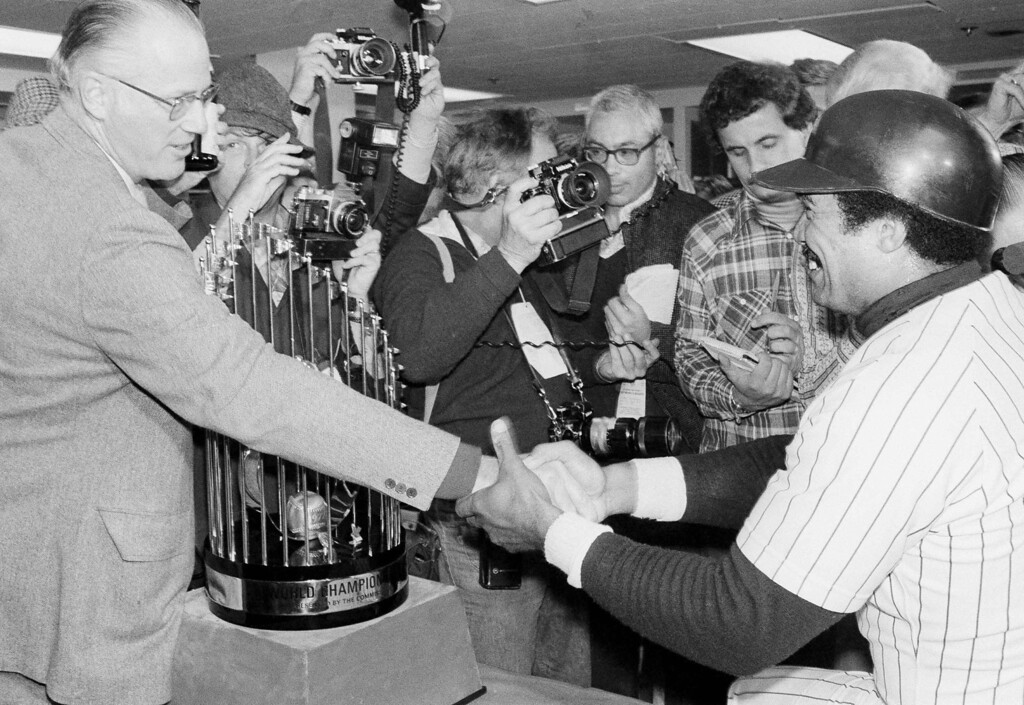 . Yankees Reggie Jackson shakes hands with Baseball Commissioner Bowie Kuhn as Kuhn congratulates him after the Yankees won the World Series over the Dodgers in New York, Oct. 18, 1977. Between them is the World Series trophy. (AP Photo)