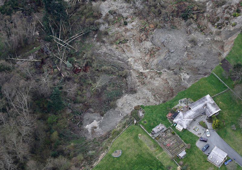 . In this aerial photo, a house sits near the bottom edge of a landslide near Coupeville, Wash. on Whidbey Island, Wednesday, March 27, 2013. The slide severely damaged one home and isolated or threatened more than 30 on the island, about 50 miles north of Seattle in Puget Sound. No one was reported injured in the slide, which happened at about 4 a.m. Wednesday. (AP Photo/Ted S. Warren)