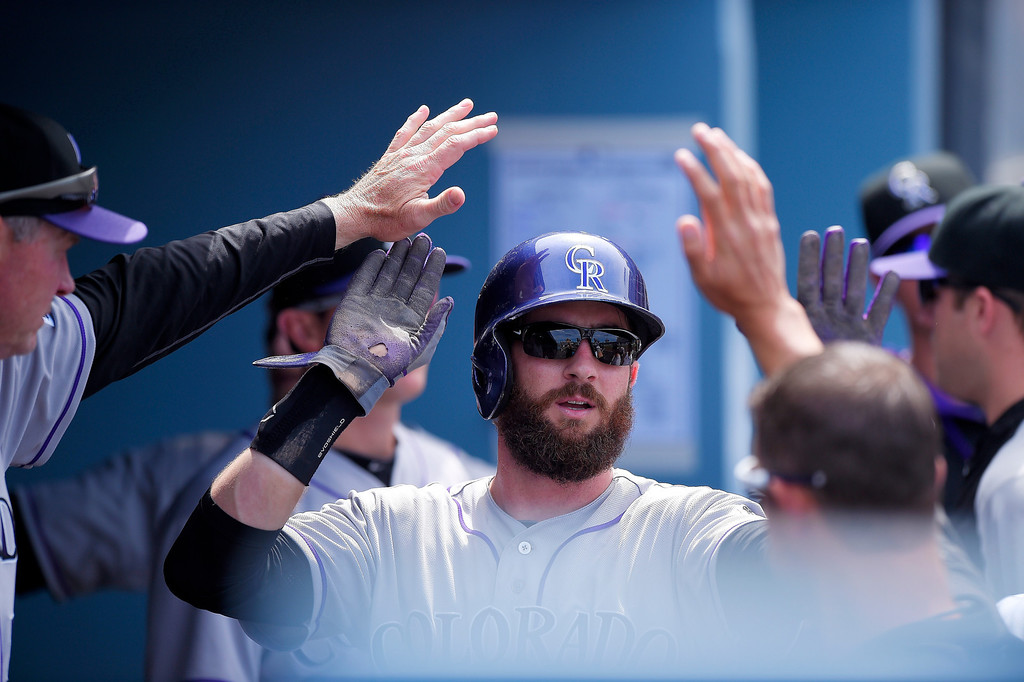 . Colorado Rockies\' Charlie Blackmon is congratulated after scoring after Brandon Barnes was caught stealing second during the fifth inning of a baseball game against the Los Angeles Dodgers, Sunday, April 27, 2014, in Los Angeles. (AP Photo/Mark J. Terrill)
