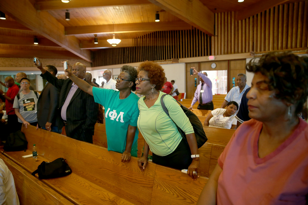 . People listen as Dr, Michael Baden, a medical examiner who carried out the autopsy on Michael Brown, speaks about the autopsy during a press conference at  the Greater St. Marks Family Church on August 18, 2014 in Ferguson, Missouri. Unarmed teenager Michael Brown was shot and killed by a Ferguson police officer on August 9th.  (Photo by Joe Raedle/Getty Images)
