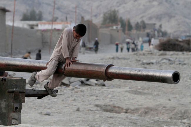 Description of . An Afghan child plays on the barrel of a Soviet tank in the Behsood district of Jalalabad, Afghanistan, Monday, Feb 18, 2013. Despite being a mineral-rich country, four decades of war have left Afghanistan as one of the least developed countries in the world and highly dependent on foreign aid. (AP Photo/Rahmat Gul)