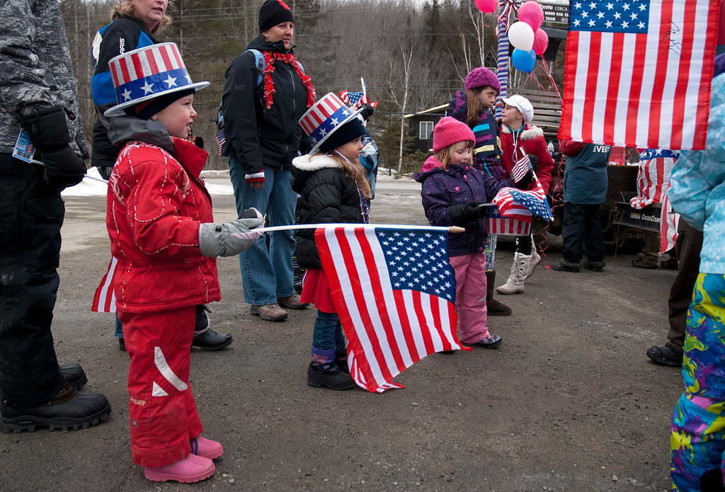 """. Kayla Rice/Reformer                                 Patriotically dressed children hold American flags for the \""""Devin Day\"""" parade and celebration in Dover on Saturday."""