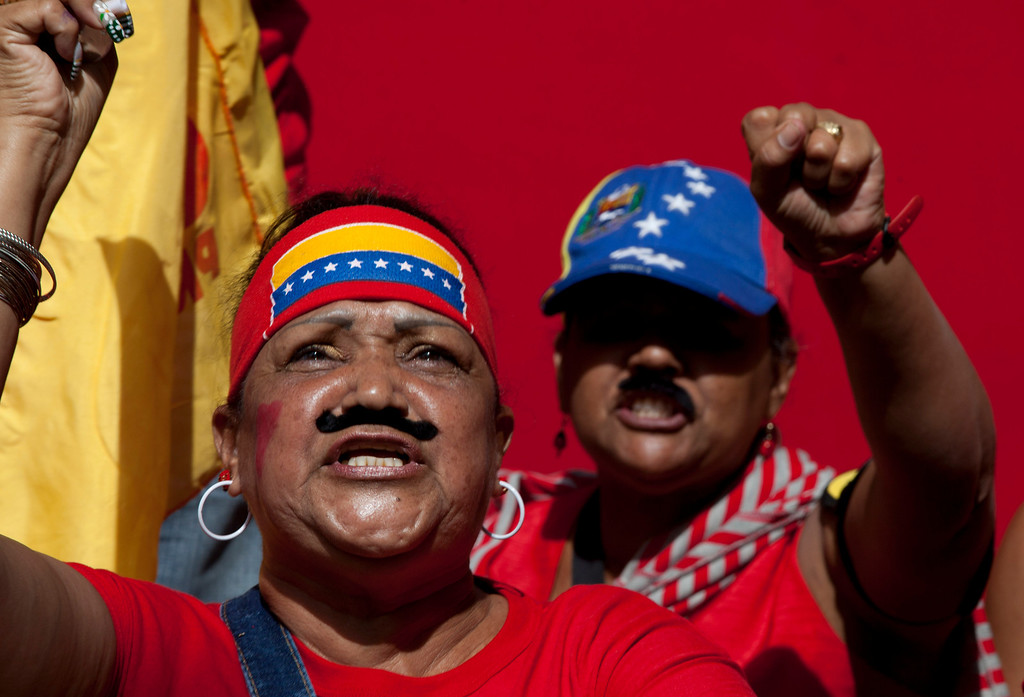 . Supporters of Venezuela\'s President-elect Nicolas Maduro wear fake Maduro-style moustaches as they shout slogans outside the parliament building prior to his inauguration ceremony in Caracas, Venezuela, Friday, April 19, 2013. Venezuela\'s ruling party moved to cement its grip on power Friday, packing thousands of red-clad supporters into the streets outside the inauguration of late leader Hugo Chavez\'s hand-picked successor. (AP Photo/Enric Marti)