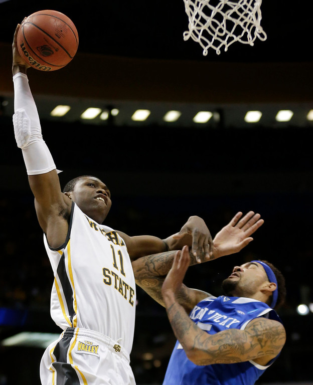 . Wichita State forward Cleanthony Early (11) goes up to dunk over Kentucky forward Willie Cauley-Stein (15) during the first half of a third-round game of the NCAA college basketball tournament Sunday, March 23, 2014, in St. Louis. (AP Photo/Charlie Riedel)