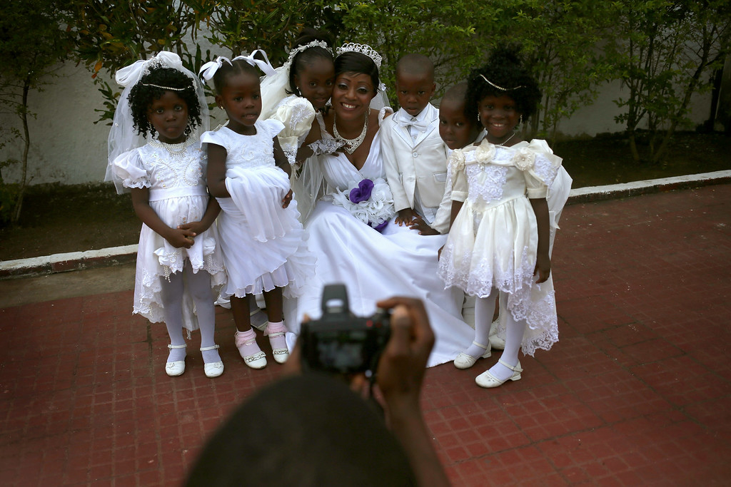 . Bindu Quaye poses for photos with flower girls before her wedding reception on January 24, 2015 in Monrovia, Liberia. Like many couples, Quaye and her groom Clarence Murvee waited until the worst of the Ebola epidemic had passed before scheduling their wedding. In order to control the outbreak, the government and international aid agencies discouraged public gatherings and physical touching. With Ebola cases now in single digits nationwide, people have begun to return to normal life.  (Photo by John Moore/Getty Images)
