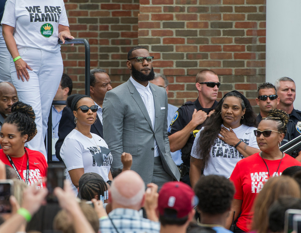 . LeBron James, center stands with his wife Savannah, left, and his mother, Gloria, right before speaking at the opening ceremony for the I Promise School in Akron, Ohio, Monday, July 30, 2018. The I Promise School is supported by the The LeBron James Family Foundation and is run by the Akron Public Schools. (AP Photo/Phil Long)