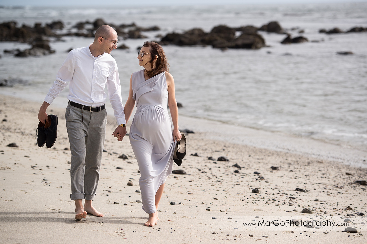 man and pregnant woman in gray dress walking on the Moss Beach during maternity session